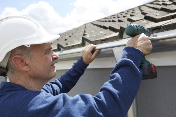 depositphotos 79060420 stock photo workman replacing guttering on exterior